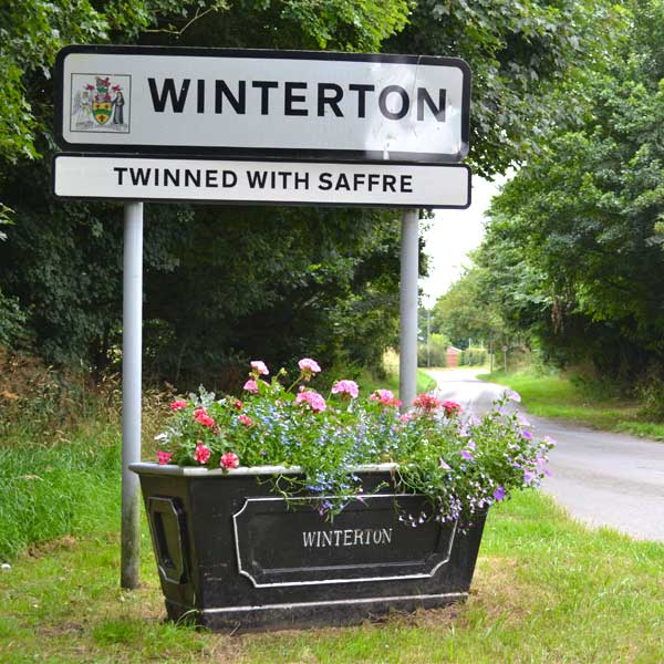 Winterton Town sign with planter in full bloom at its base