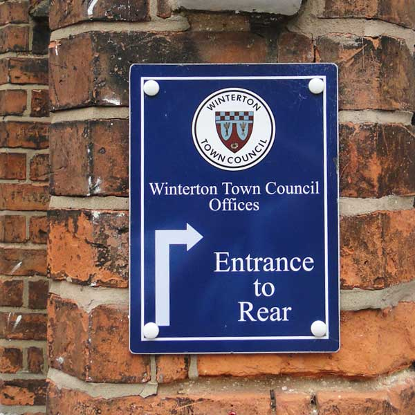 Sign on the wall of Winterton Town Council Offices showing the route to the entrance