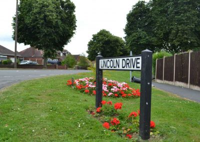 Lincoln Drive road sign next to a flower bed in full bloom